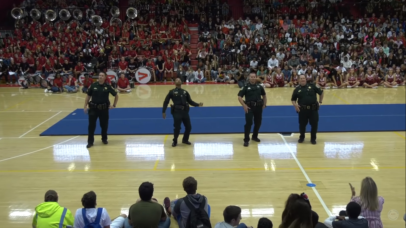 Cops walk onto gym floor & show off their dance moves
