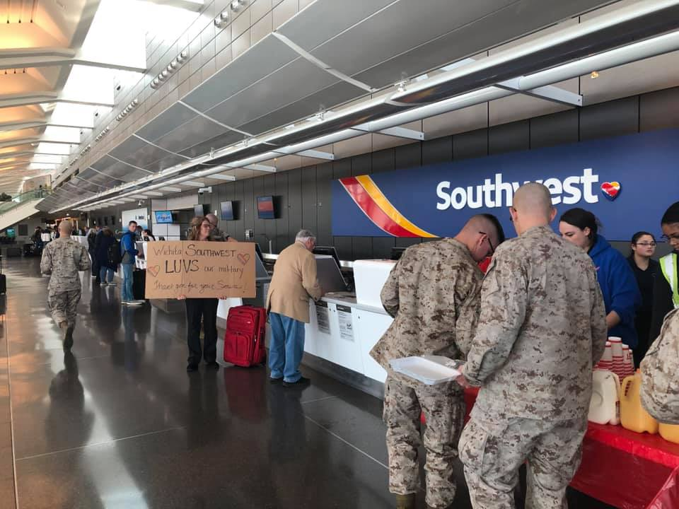 US Military Troops Takes Breakfast At Southwest Airlines Booth & Woman Employee Hold A Thank You Sign