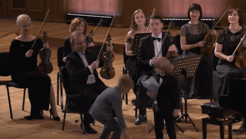 Little Boy Sits At Piano Leads Orchestra In Mozart Performance For A Standing Ovation