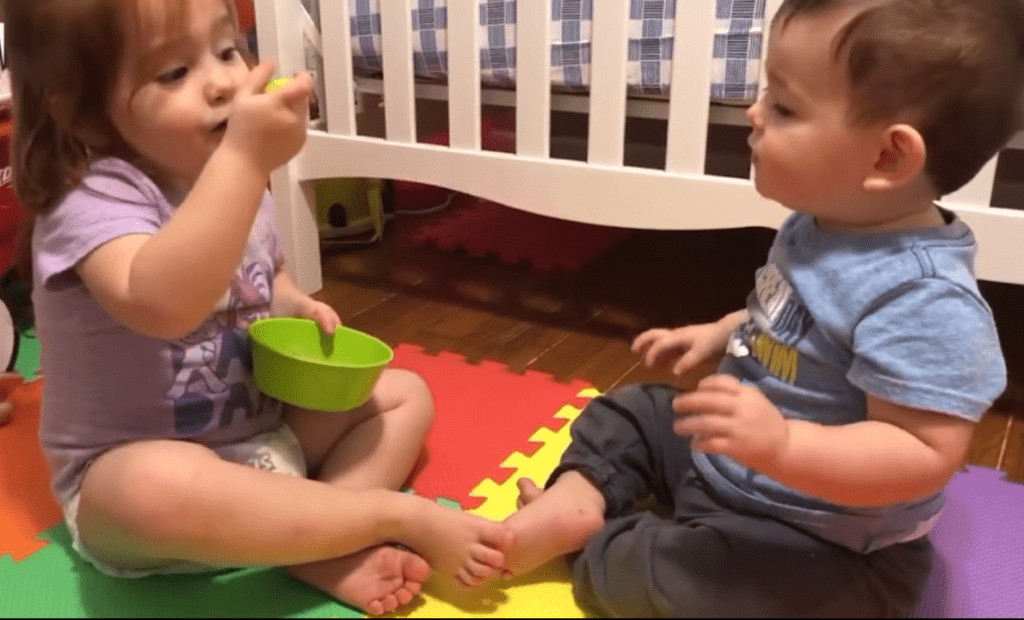 Toddler Sister Shares Her Food with Young Baby Brother
