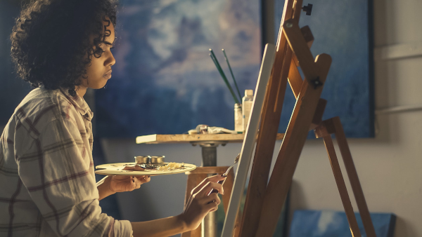 Woman painting at a canvas