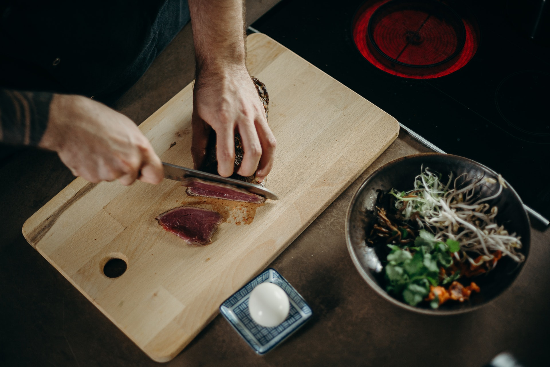 https://www.pexels.com/photo/person-slicing-meat-on-wooden-chopping-board-3298633/